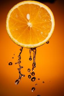 Долька апельсина и всплеск сока, изолированные на цветном фоне