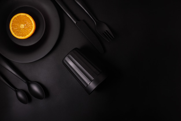 Orange slice on black plate with black glass and black cutlery on black background, top view