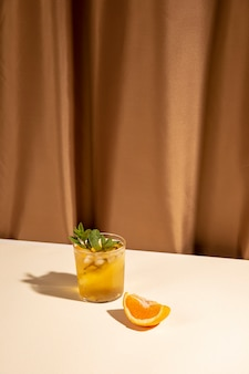 Orange slice and cocktail drink glass on white table near brown curtain