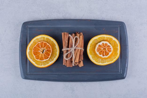 Fetta d'arancia a bordo scuro con bastoncini di cannella aromatici.