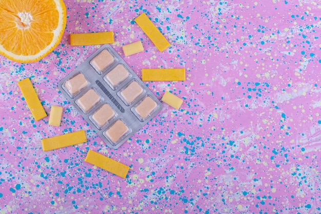 Fetta d'arancia, una manciata di gomme da masticare e un pacchetto di compresse di gomma su una superficie colorata