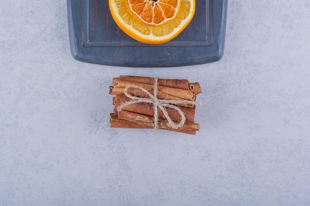 Долька апельсина на темной доске с ароматными палочками корицы.