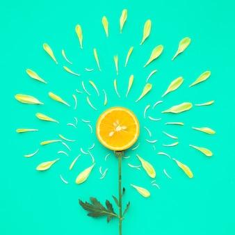 緑の平らな場所に花びらが付いたオレンジスライス