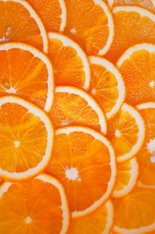 Апельсин нарезанный кружочками. фон залит оранжевым.