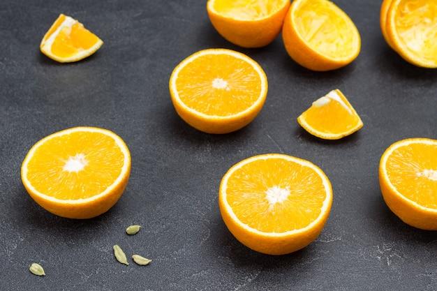 テーブルの上でスライスされたオレンジ。黒の背景。上面図。