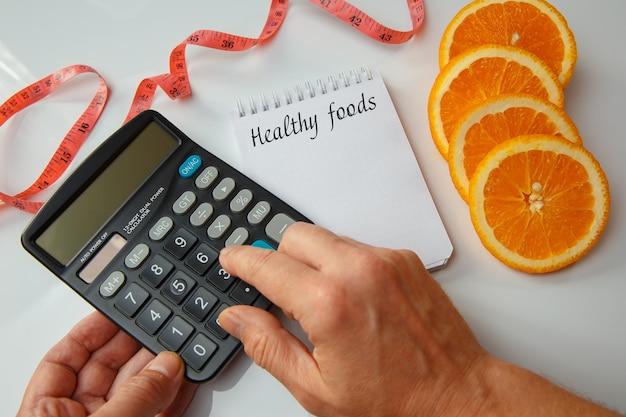 오렌지 조각, 빈 메모 및 측정 테이프. 계산기에서 계산하는 칼로리. 다이어트 개념