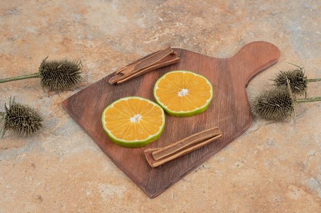 Дольки апельсина и палочки корицы на деревянной доске.