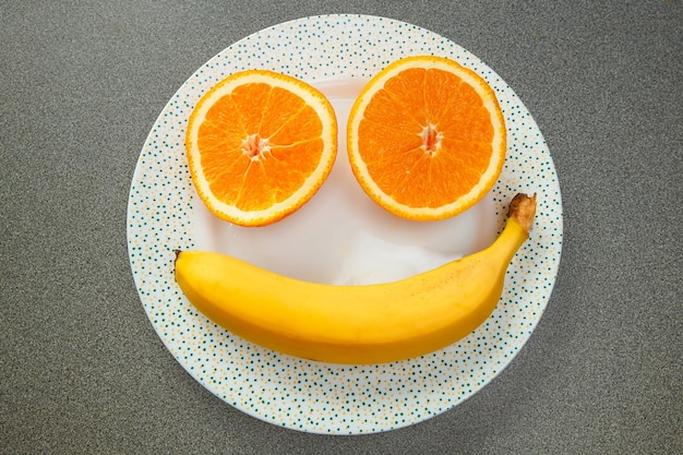Orange slices and a banana in the shape of a smiley face