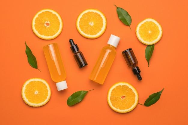 Ломтики апельсина, бутылки с лекарствами и бутылки сока на оранжевом фоне.