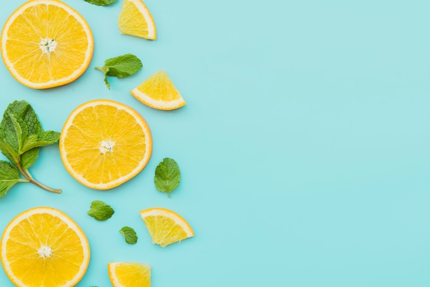 Orange slices and mint leaves on background