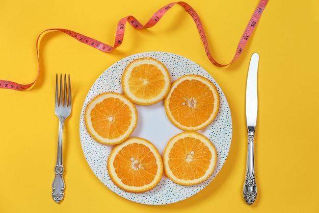 접시와 포크로 칼에 오렌지 슬라이스. 다이어트 개념