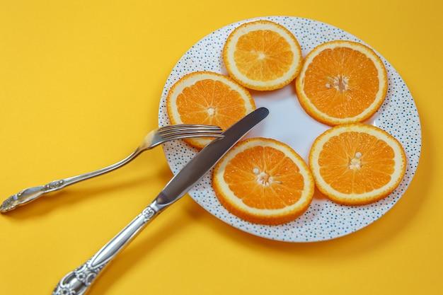 皿の上のオレンジスライスとフォーク付きのナイフ。ダイエットコンセプト