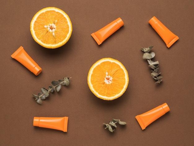 Дольки апельсина, трубочки сливок и веточки эвкалипта на коричневом фоне. плоская планировка.