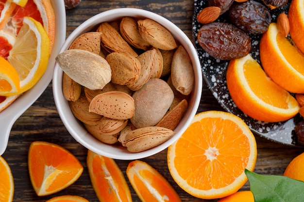 Orange slices with dates, almonds, grapefruit slices and leaf in plates on wooden table, flat lay.