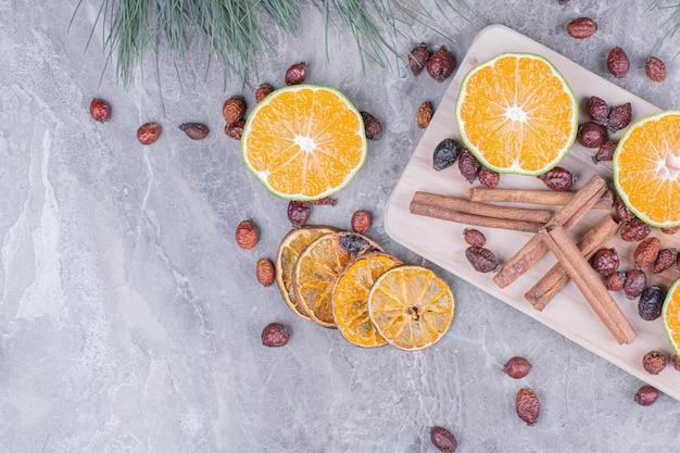 Fette d'arancia con fianchi e cinnamons su un piatto di legno