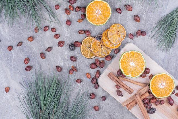 Orange slices with hips and cinnamons on a wooden platter