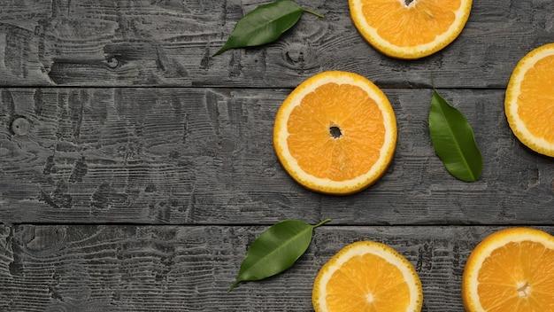 Дольки апельсина с листьями на деревянном фоне. место для текста. популярный тропический фрукт. плоская планировка.