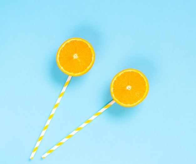 Orange slices with tubules, healthy candy on a stick, lollipops, light blue background, flat lay, minimalism