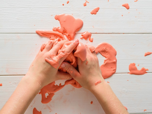 Orange slime spreads from the hands of a child on a white table.