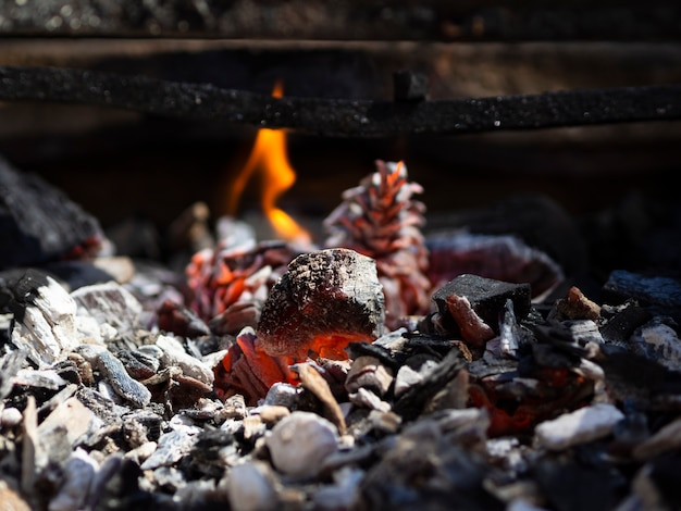 Orange smoldering coals and low flame in barbecue