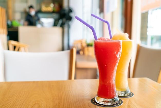 Апельсиновый смузи и стакан смузи из арбуза в кафе-ресторане