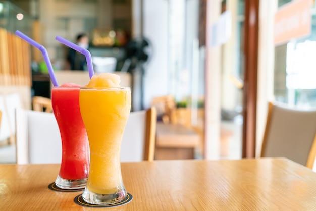 カフェレストランのオレンジ色のスムージーとスイカのスムージーグラス