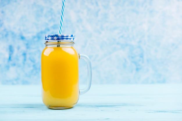 Orange smoothie in a jar copy space