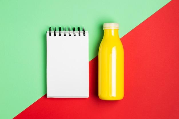 Orange smoothie with empty notepad