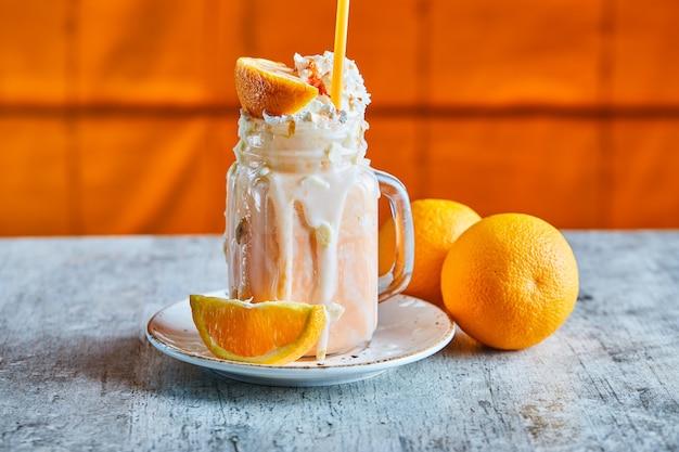 흰색 접시에 뿌리와 짚 오렌지 스무디