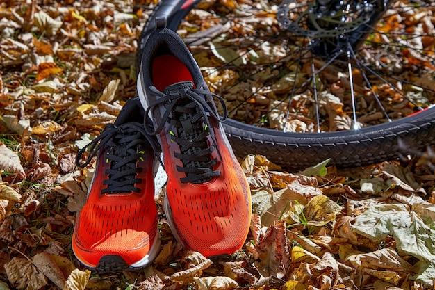 秋の秋の背景にオレンジ色のスニーカーと自転車の車輪
