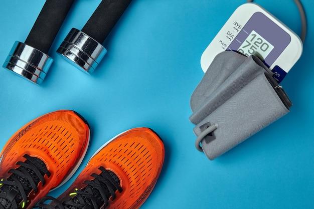 Оранжевые кроссовки, гантели и тонометр на синем фоне. физические упражнения и артериальное давление