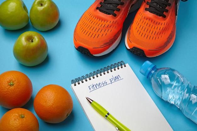 파란색 배경에 주황색 운동화 과일과 물 한 병
