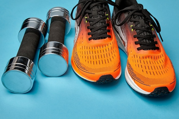 Orange sneakers and metal dumbbells on a blue background