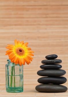 黒い石のスタックの横にあるガラスフラスコのオレンジのひまわり