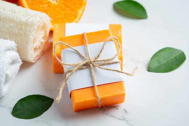 Апельсиновое мыло со свежим апельсином на мраморном фоне