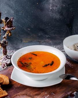 灰色の表面の白い深いプレートの内側でおいしいオレンジスープ