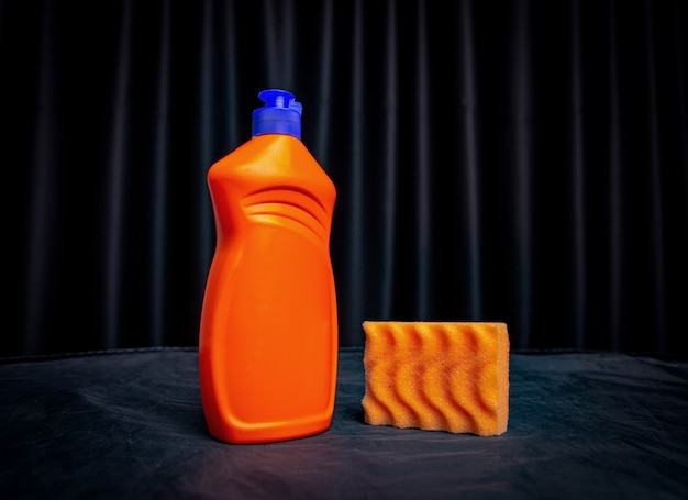 Orange sponge with cleaning agent on black surface