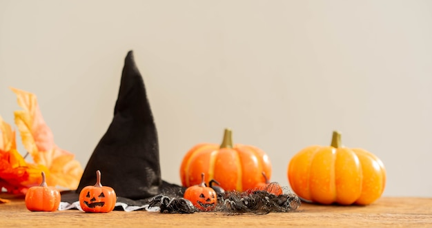 ハロウィーンのコンセプトのためのクモと魔女の帽子とカエデの葉とオレンジ色の不気味なカボチャ