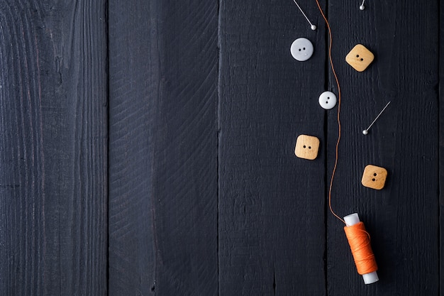 Orange spool of thread, pins and buttons for sewing on a wooden black background. copy space