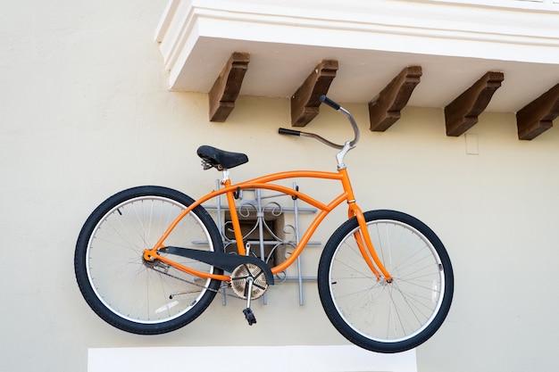 誰もいない屋外の白い壁にぶら下がっている鉄の船体とゴム製のタイヤの車輪が付いているオレンジ色のスポーツ自転車