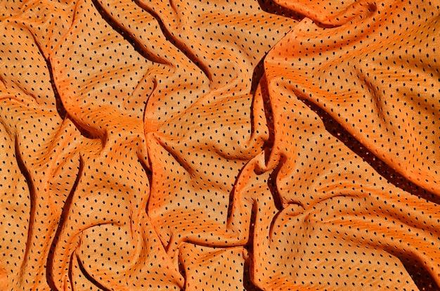 Оранжевая предпосылка текстуры ткани одежды спорта. взгляд сверху оранжевой поверхности ткани ткани.