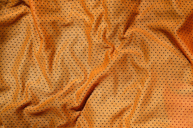 Orange sport clothing fabric texture background. top view