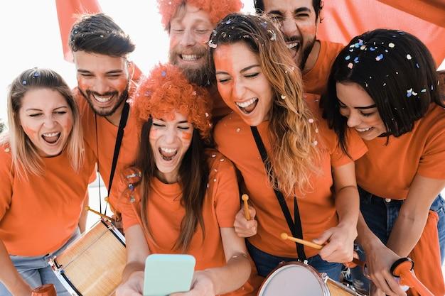 휴대 전화로 축구 경기를 보는 오렌지 스포츠 서포터-중앙 여자 얼굴에 주요 초점