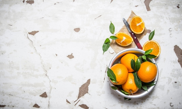 오렌지 스타일. 컵에 잎을 가진 신선한 오렌지입니다.