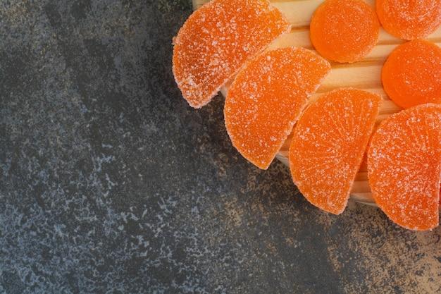 Сладкий мармелад апельсинового сахара на деревянной тарелке. фото высокого качества