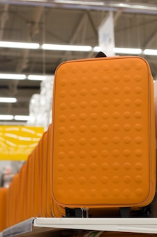 Orange suitcases sale in a shop