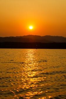 Оранжевое солнце спускается к закату над горой и отражается на реке с затенением далекого дерева.