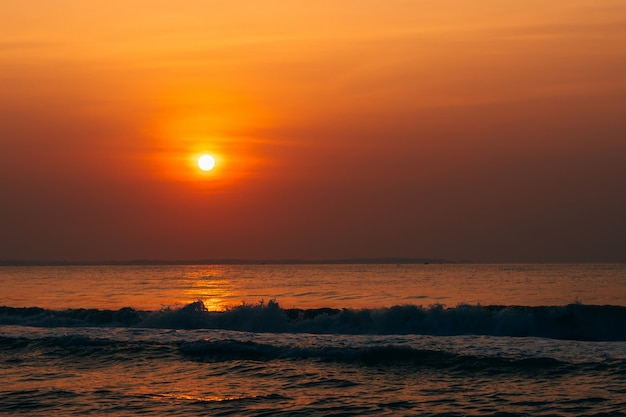 Orange sunrise against the sea with waves