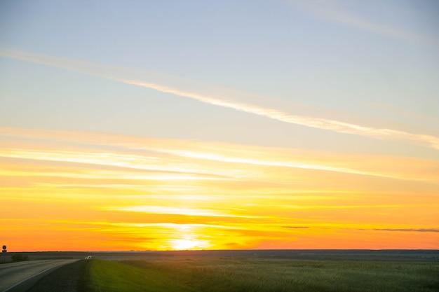오렌지 일몰 추상화입니다. 푸른 하늘, 태양, 구름. 해가 거의 수평선 너머에 있다