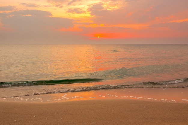 Orange sunset over the calm sea. green wave runs onto a sandy beach